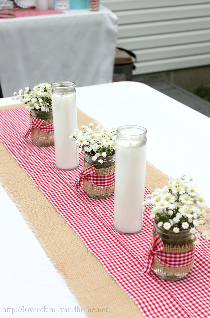 Inexpensive jar candles from the dollar tree & mason jars wrapped in burlap with red gingham bow. Simple & easy table decor for western/cowboy themed party.